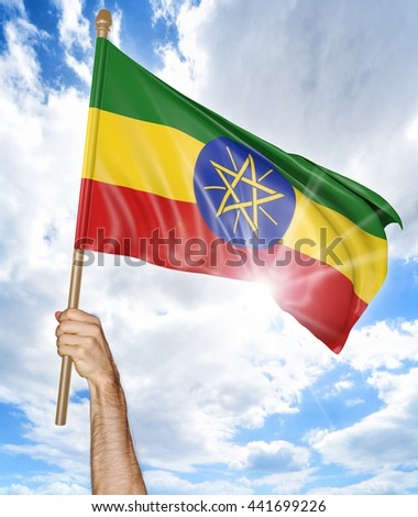 Person's hand holding the Ethiopian national flag and waving it in the sky, 3D rendering - stock photo