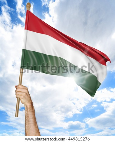 Person's hand holding the Hungarian national flag and waving it in the sky, 3D rendering - stock photo