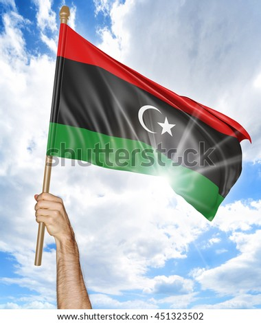 Person's hand holding the Libya national flag and waving it in the sky, 3D rendering - stock photo