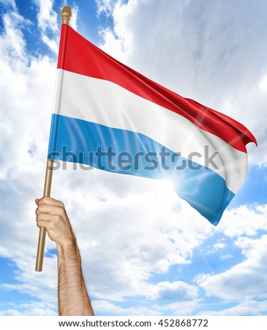 Person's hand holding the Luxembourg national flag and waving it in the sky, 3D rendering - stock photo