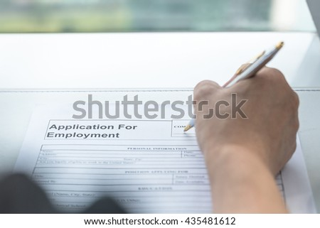 Person's hand with ballpoint pen writing on blank application for employment form paper: Fill in empty document register applying for a job, human resources, finance, loan, mortgage business concept - stock photo