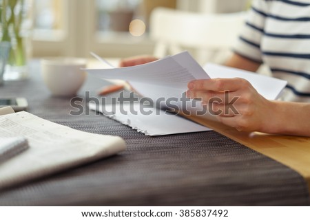 Person seated at a table with a cup of coffee reading a paper document, close up view of the hands - stock photo