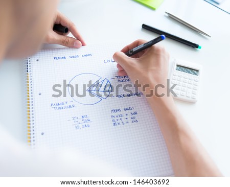 Person sitting at the desk, calculating sales earnings and drawing circular diagram with numbers - stock photo