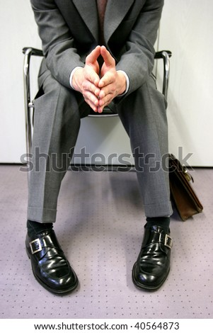 Person sitting impatiently, waiting for a job interview - stock photo