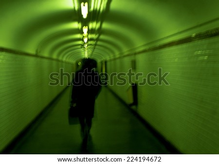 Person walking in subway tunnel, Paris, France - stock photo