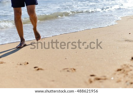 Person walking on summer beach outdoors background. Male in swimming shorts