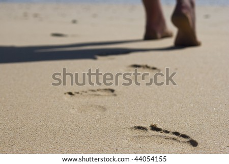 Person walking on the beach - stock photo