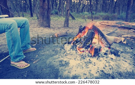Person warms their feet next to a campfire at dusk camping in the woods with Instagram style filter - stock photo