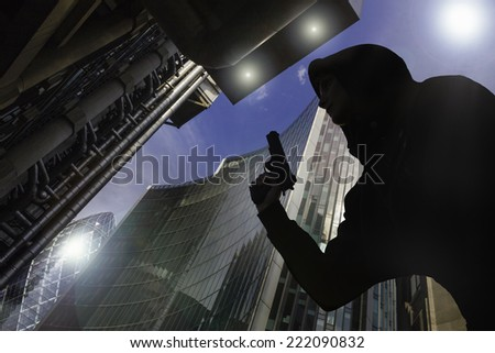Person wearing a hoodie, walks through a city with gun - stock photo