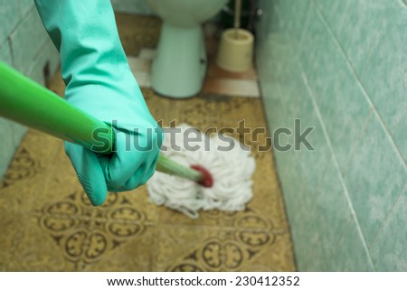 Person wearing a turquoise rubber glove, cleaning toilet with mop  - stock photo