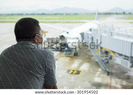 Person wearing protective mask against transmissible infectious diseases and as protection against pollution and the flu at airport. Asian man commuter in airport public area. - stock photo