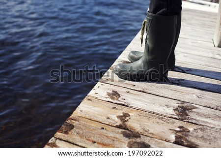 Person wearing wellingtons at jetty, close-up - stock photo