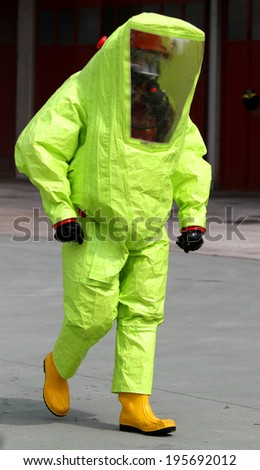 person with anti radiation suit yellow and yellow rubber boots to guard against the risk of bacteriological and chemical biological attack - stock photo