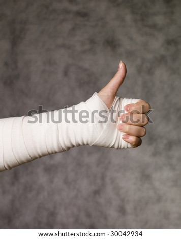 Person with bandage doing thumbs up - stock photo