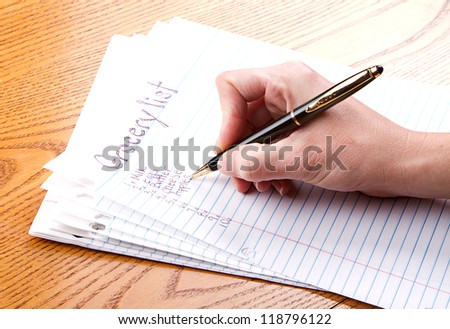 person writing grocery list - stock photo