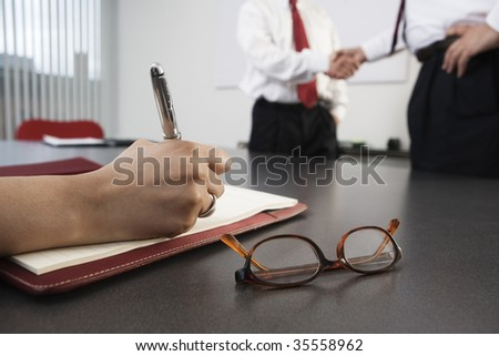 Person writing with business men shaking hands in the background.