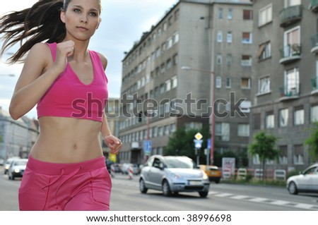 Person (young beautiful woman) running and training in city street - stock photo