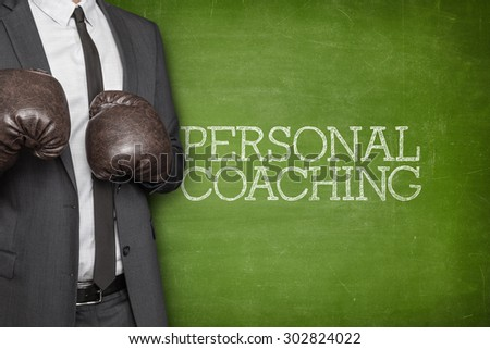 Personal coaching on blackboard with businessman wearing boxing gloves - stock photo