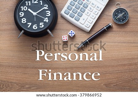 Personal Finance words written on wooden table with clock,dice,calculator pen and compass - stock photo