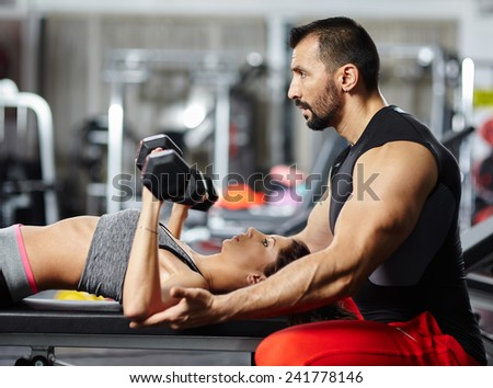 Personal fitness trainer assisting a young woman in the gym at a workout - stock photo