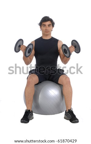 Personal fitness trainer (coach) sitting on a power ball exercising with dumbbells over white background - stock photo