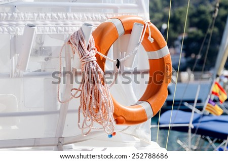 Personal flotation device on yacht aft with rope - stock photo