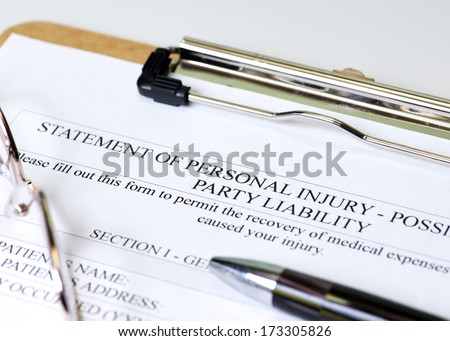Personal injury claim on clipboard with pen and glasses. - stock photo