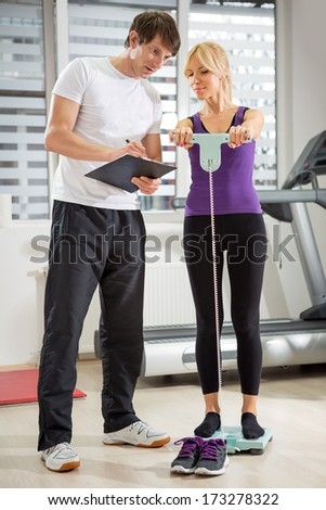 personal instructor checking results about progress in training - stock photo