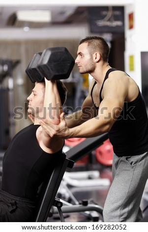 Personal instructor helping athletic young man work with heavy dumbbells