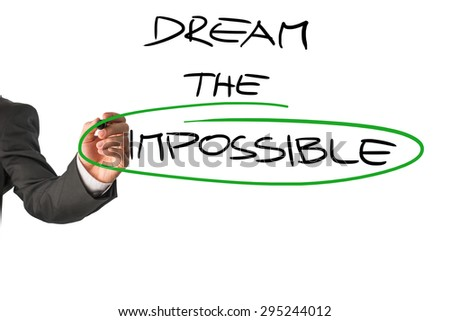 Personal motivator writing a Dream the impossible message, with a special emphasis on the word Impossible,  on a white virtual screen encouraging you to allow yourself to live to your full potential. - stock photo