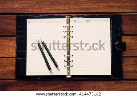Personal organizer with pen and pencil on wooden table background, flat lay, workplace and business concept - stock photo