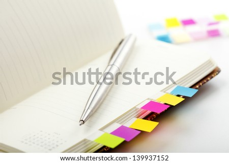 Personal planner (organizer) with colorful bookmarks on office desk. Shallow focus. - stock photo