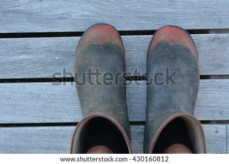 Personal point of view of mans gardening gumboots on wooden panels . Copyspace - stock photo