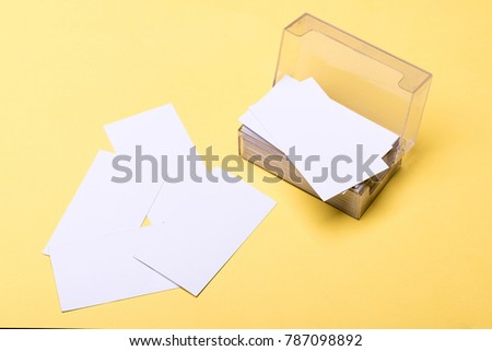 Personal presentation accessory in close up. Business contacts concept. Business cards stack in card holder on yellow background. Name cards in white color with copy space.