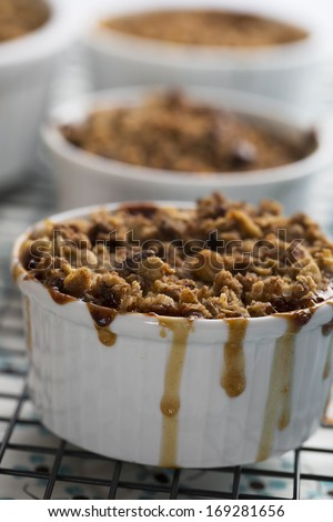 Personal sized apple crumble with filling dripping down the sides. - stock photo