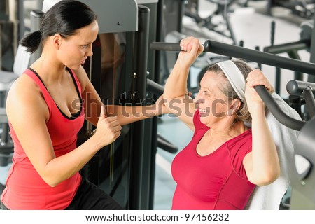 Personal trainer assist senior woman exercising on machine at gym - stock photo