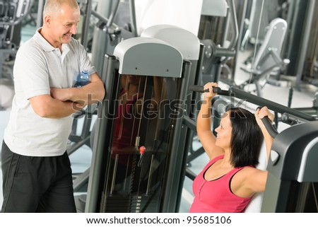 Personal trainer at fitness center showing exercise to active man