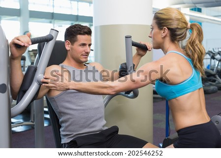 Personal trainer coaching bodybuilder using weight machine at the gym - stock photo