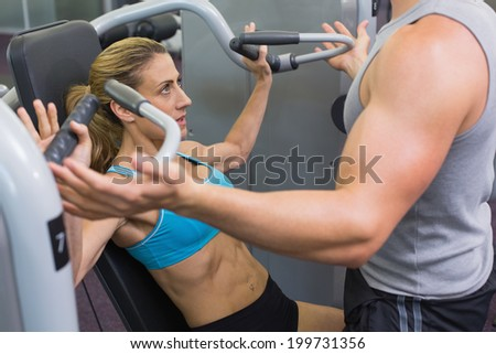 Personal trainer coaching female bodybuilder using weight machine at the gym - stock photo