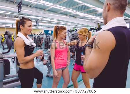Personal trainer encouraging to sad young woman after a hard training day in the gym - stock photo