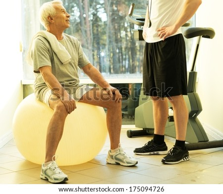 Personal trainer explains to a senior man how to do exercise on a fitness ball - stock photo