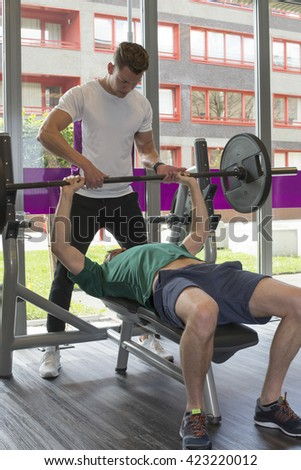Personal trainer giving advice to  man during dumbbell weight training equipment at a gym