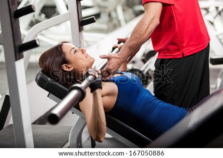 Personal trainer helping a young woman lift a barbell while working out in a gym - stock photo