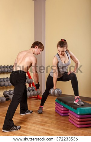Personal trainer helping girl learn exercise with dumbbells. Fitness club. Slimming program. Health & Fitness. - stock photo
