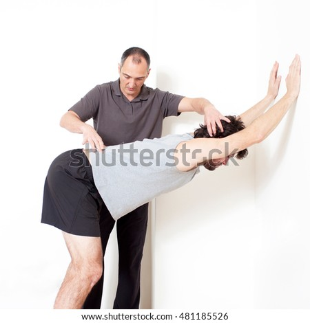 Personal trainer helping with stretching exercise