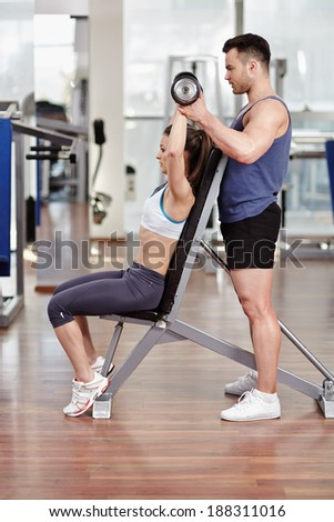 Personal trainer helping woman working with dumbbells - stock photo
