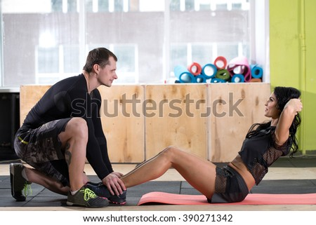 personal trainer in a gym helps do the exercise