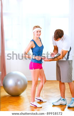 Personal trainer measuring belly of girl in sportswear - stock photo
