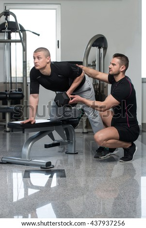 Personal Trainer Showing Young Man How To Train Back Exercise With Dumbbell In A Health And Fitness Concept - stock photo