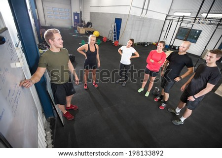 Personal trainer teaches his fitness workout team - stock photo